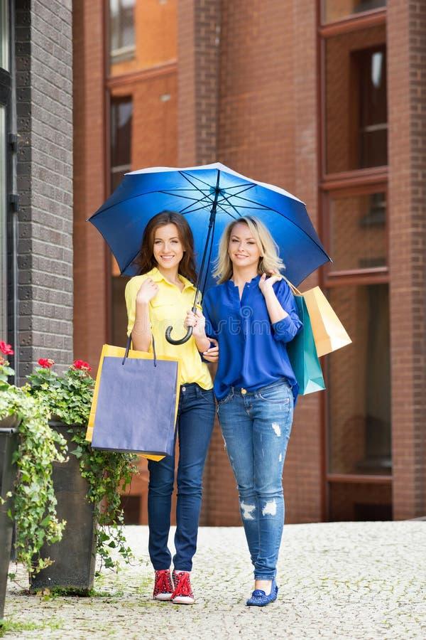 Full längd för två härliga kvinnliga vänner som går med ett paraply och shoppingpåsar fotografering för bildbyråer