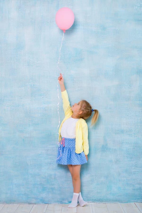 Full längd Gullig liten flicka som rymmer en rosa ballong på en blå bakgrund arkivbilder