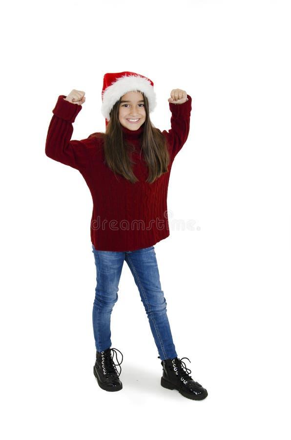Full längd på den lilla flickan i den röda julhatten med händer upp Julflicka arkivfoto