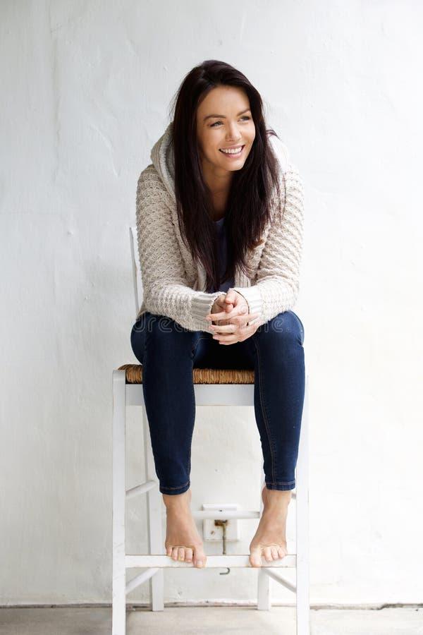Full längd som ler sammanträde för ung kvinna på stol royaltyfria foton