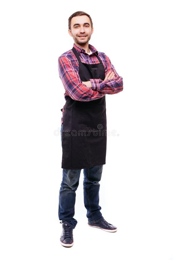 Full längd som skjutas av det unga posera bärande svarta förklädet för kock eller för uppassare och skjortan som isoleras på vit  fotografering för bildbyråer