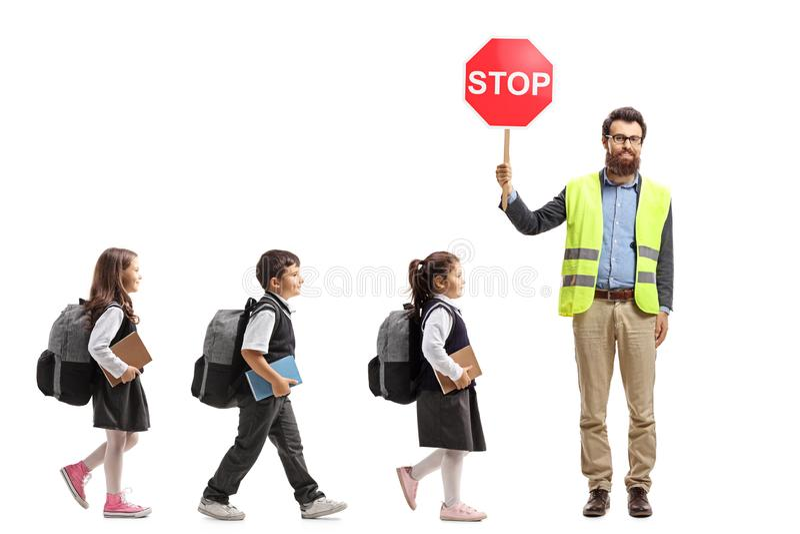Full längd som skjutas av skolbarn som går i en linje och en lärare med säkerhetsvästen, och stopptecknet som isoleras på vit bak royaltyfri foto