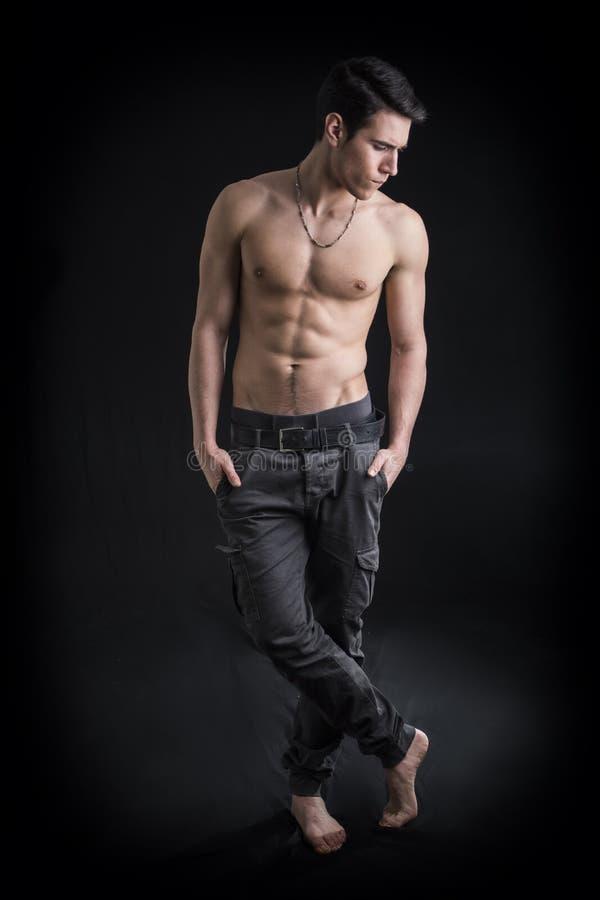 Full längd som skjutas av stiligt, shirtless ung man för passform som bär endast flåsanden fotografering för bildbyråer
