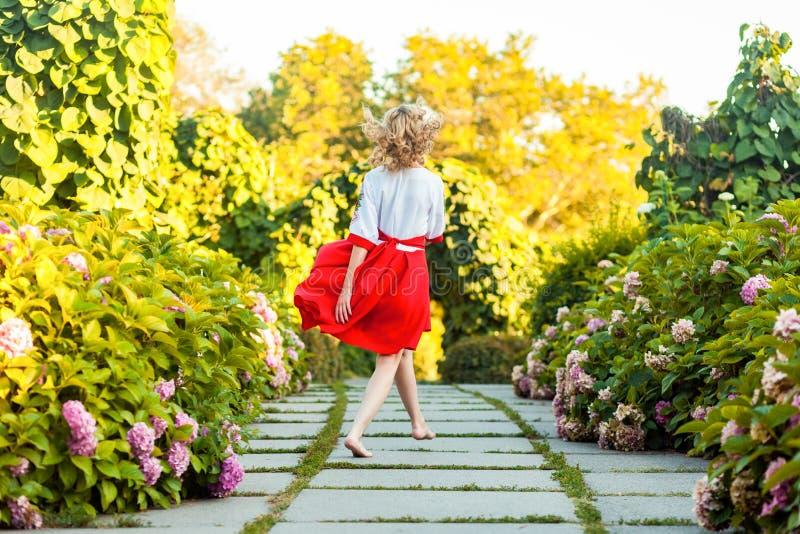 Full längdbaksidasikt av den lyckliga oförsiktiga barfota attraktiva unga blonda kvinnan i stilfull röd vit klänning som går med  royaltyfri foto