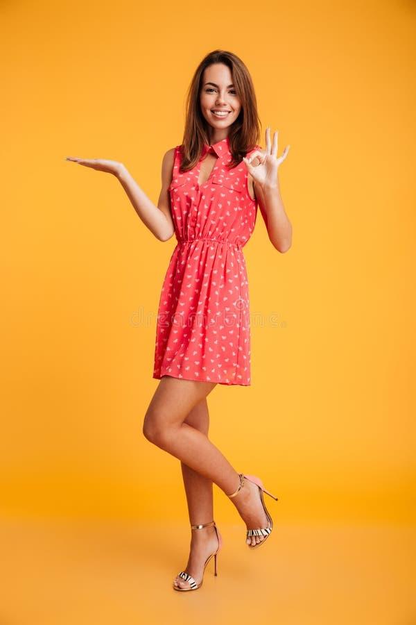 Full längdbild av att le brunett i hållande copyspace för klänning royaltyfria bilder