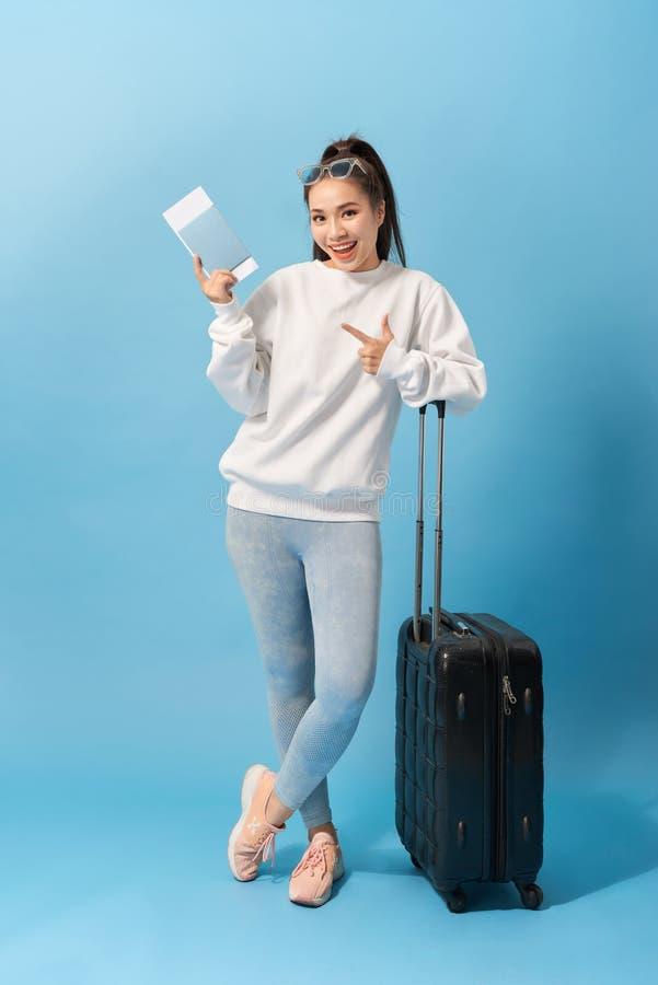 Full längdbild av den gladlynta kvinnan som bär i tillfälliga kläder som förbereder sig att snubbla med bagage och biljetter över arkivbild