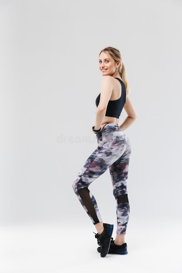 Full längdbild av den iklädda sportswearen för idrotts- blond kvinna20-tal som ler och ser kameran, medan göra genomkörare i idro royaltyfria bilder