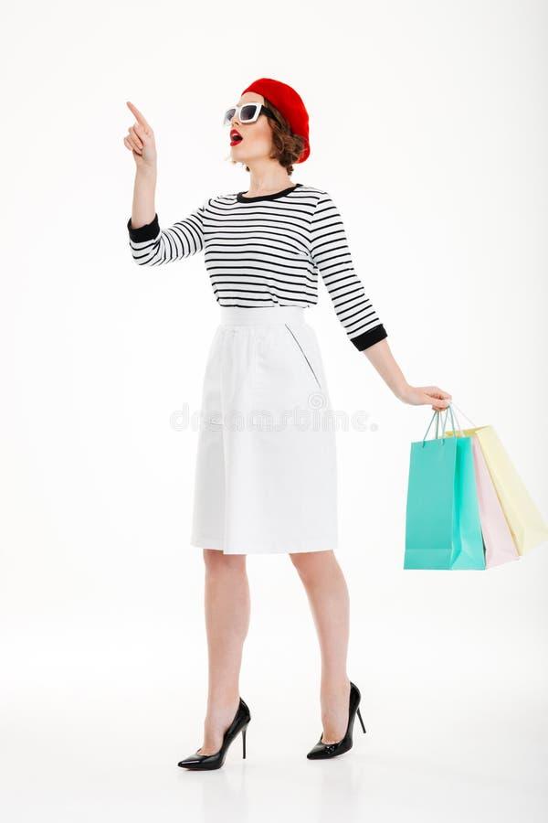 Full längdbild av den ljust rödbrun kvinnan i solglasögon med packar royaltyfri fotografi