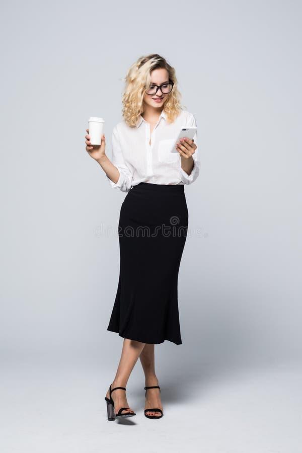 Full längdbild av den nätta affärskvinnan i formella kläder som står och använder mobiltelefonen med takeaway kaffe i hand över g royaltyfria bilder