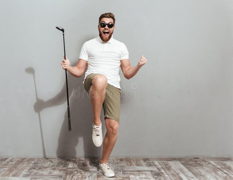 Full längdbild av en lycklig skrikig golfare i solglasögon arkivfoto