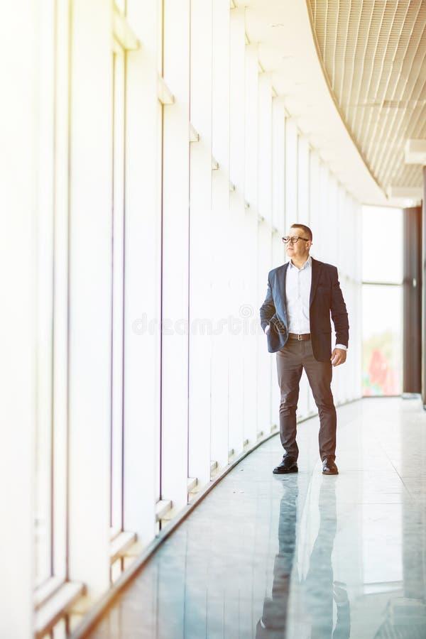 Full längdbild av en mitt- åldrig affärsman som går in mot kameran och i regeringsställning ler byggande arkivbilder