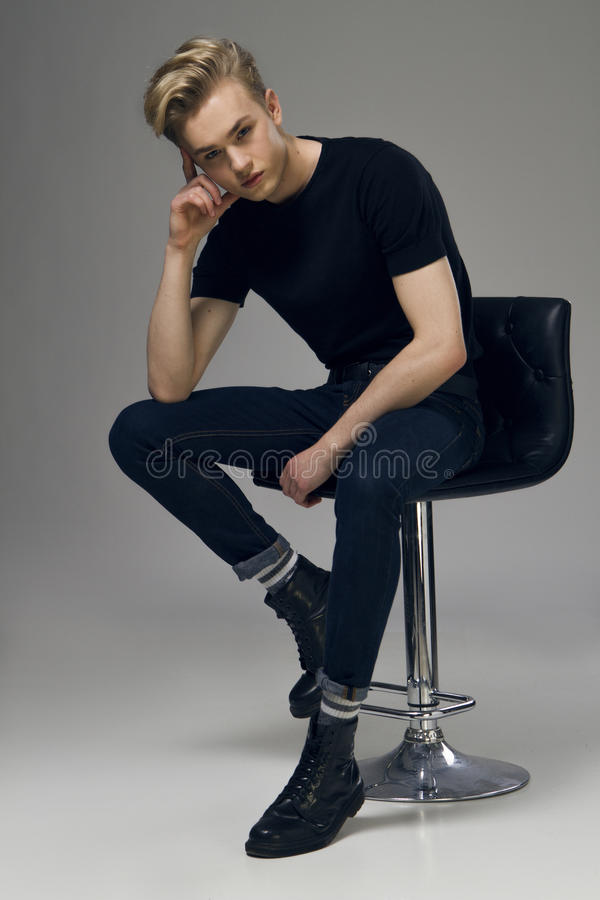 Full längdbild av ett ungt manligt modellsammanträde på en stol arkivfoton