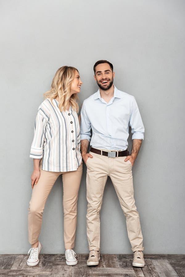 Full längdbild av lyckliga par i tillfälliga kläder som ler och ser kameran arkivfoto