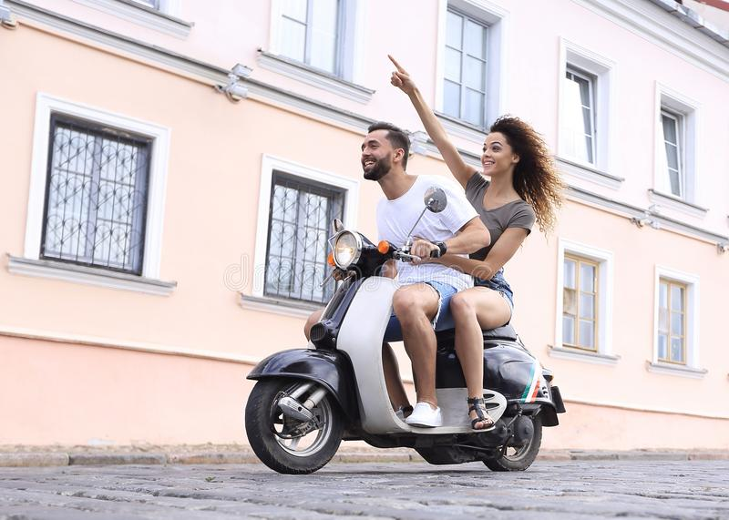 Full längdsidosikt av den lyckliga parridningen på den retro mopeden arkivfoto