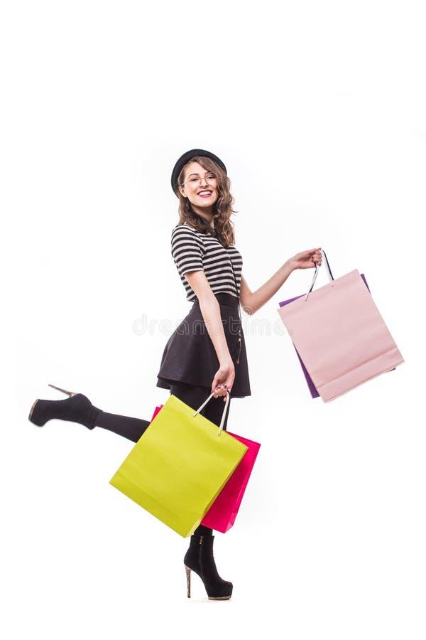 Full längdsidosikt av den unga kvinnan som går med shoppingpåsen som isoleras över vit bakgrund arkivfoton