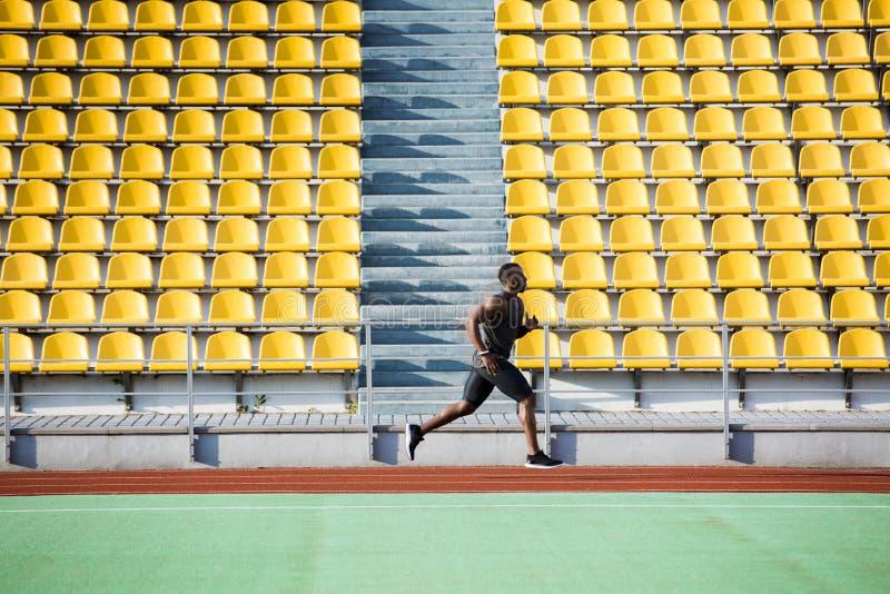 Full längdsidosikt av en idrottsmanspring på löparbana royaltyfria foton