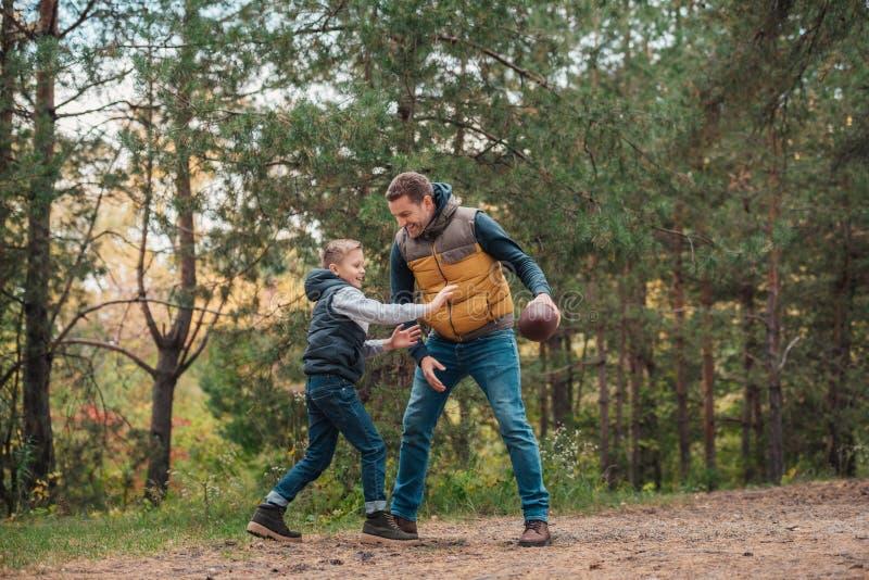 full längdsikt av den lyckliga fadern och sonen som spelar med rugbybollen royaltyfri fotografi