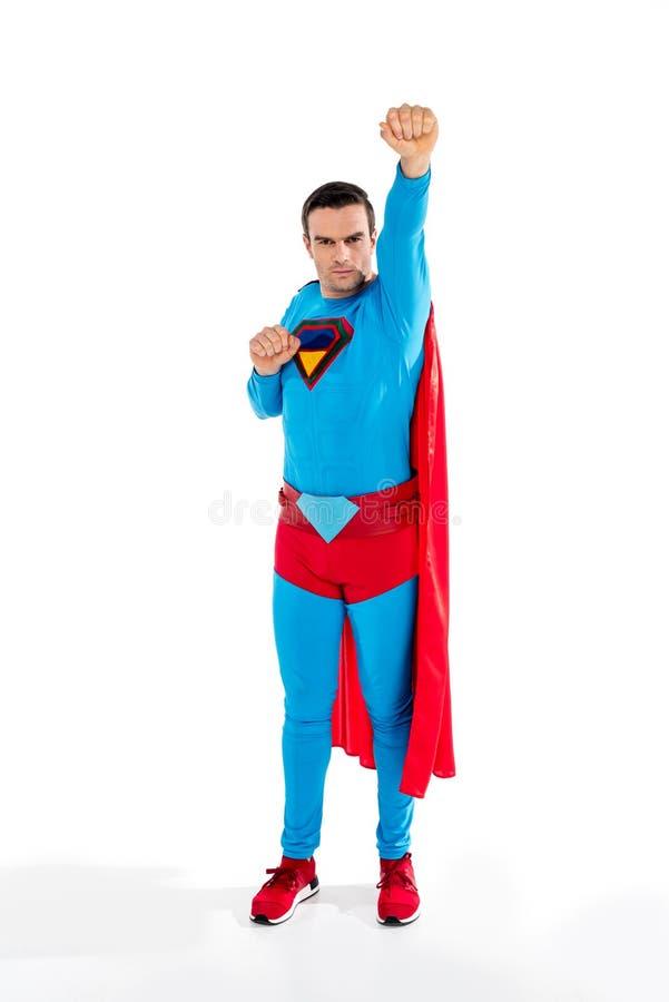 full längdsikt av den stiliga manliga superheroen som lyfter handen och ser kameran arkivfoto