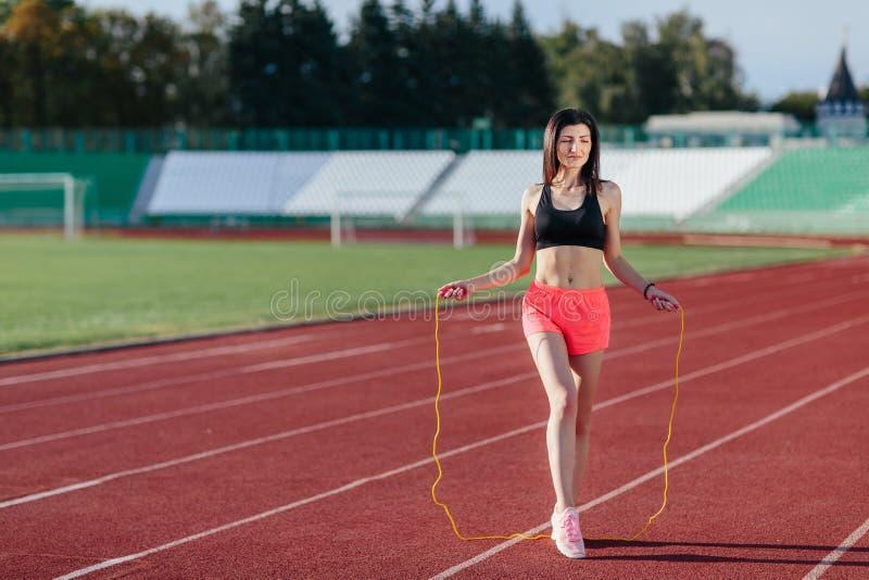 Full längdsikt av den unga sportbrunettkvinnan i rosa kortslutningar och svart överkant som övar med överhopprepet på stadion royaltyfri foto