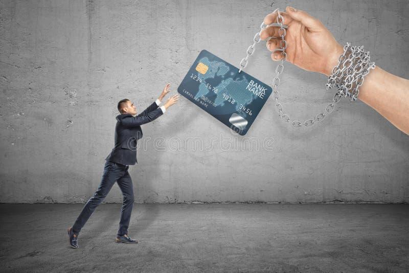Full längdsikt för sida av den lilla affärsmannen som ut når för att gripa kreditkorten som rymms på kedja av den enorma handen m royaltyfri fotografi