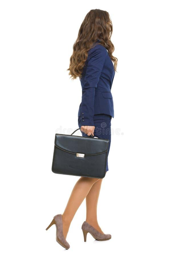 Full längdstående av affärskvinnan med att gå för portfölj arkivbilder