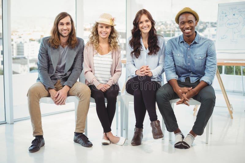 Full längdstående av att le affärsfolk som sitter på stol royaltyfria foton