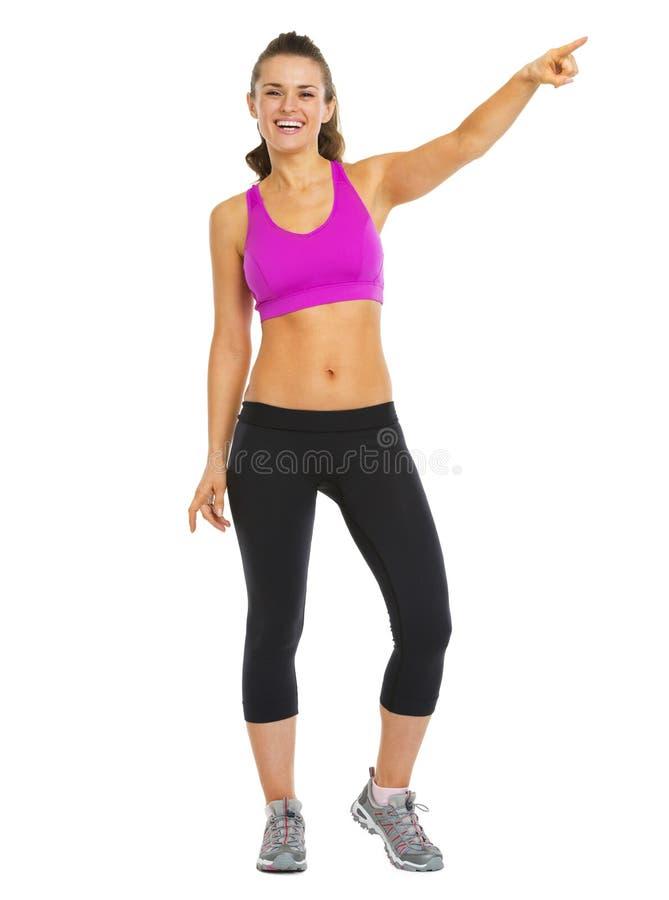 Full längdstående av att le den unga kvinnan för kondition som pekar på royaltyfri foto