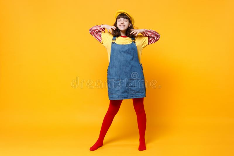 Full längdstående av att le flickatonåringen i den franska basker, grov bomullstvillsundress som håller händer nära framsidan som fotografering för bildbyråer