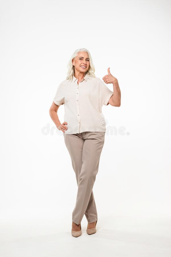 Full längdstående av att le 70-tal för vuxen kvinna med grått hår I arkivfoto