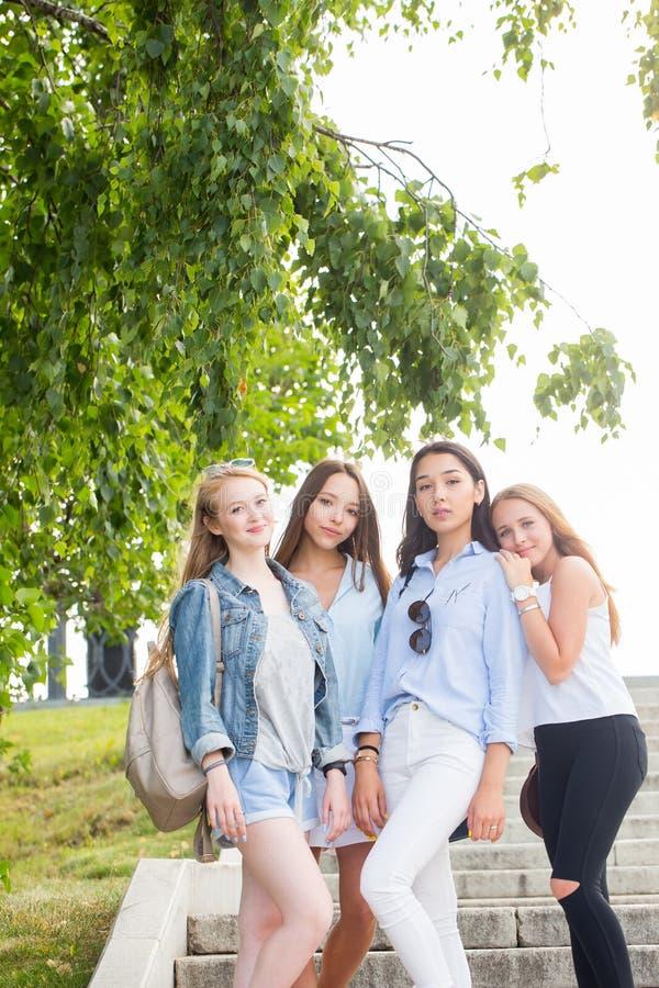 Full längdstående av charmiga unga studentflickor i parkera i sommar Färgade kläder, gymnastikskor och skor för kvinnakläder past arkivfoto