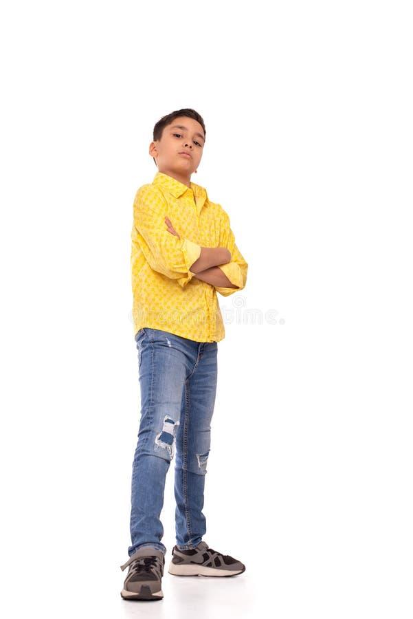 Full längdstående av den allvarliga pojken av brunetten med den armar korsad bärande gul skjortan och jeans på en vit bakgrund arkivfoton