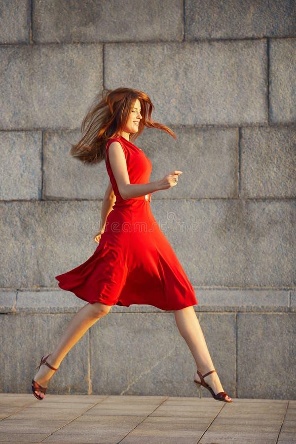 Full längdstående av den attraktiva eleganta unga kvinnan i röd klänning royaltyfri foto