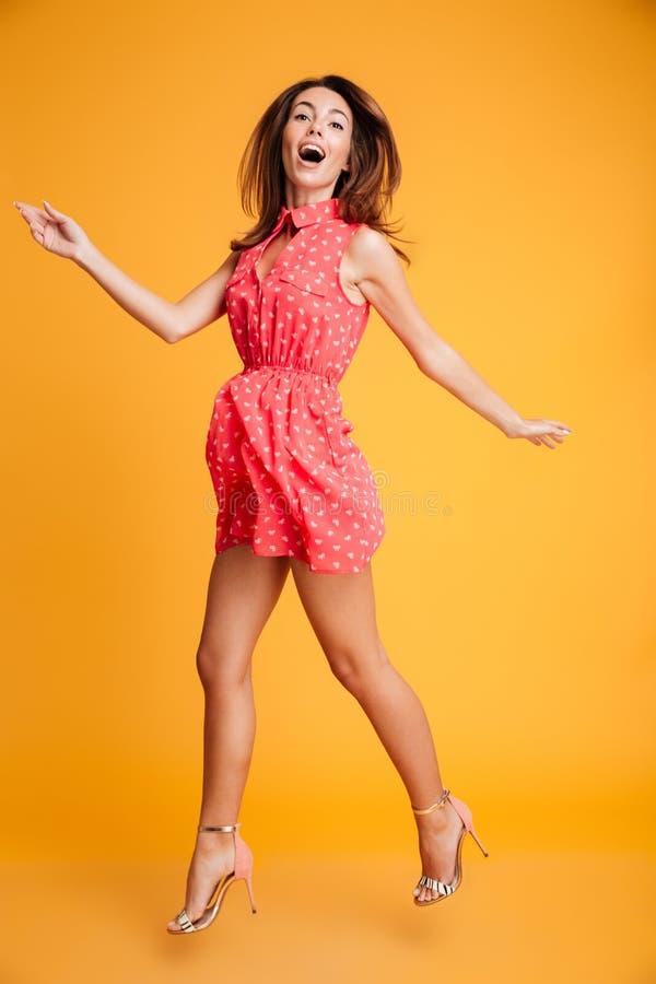 Full längdstående av den charmiga brunettkvinnan i röd klänninghav royaltyfri foto