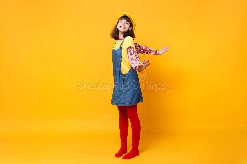 Full längdstående av den charmiga flickatonåringen i den franska basker, grov bomullstvillsundress som fördelar händer som isoler arkivbild