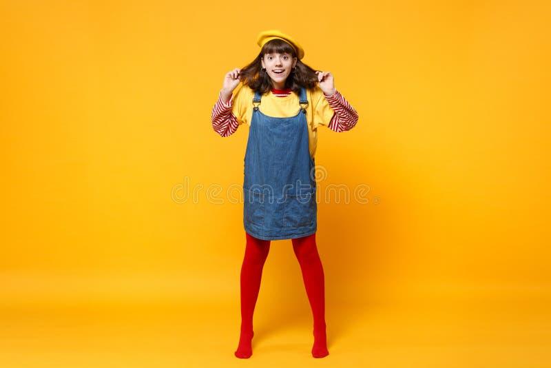 Full längdstående av den förvånade flickatonåringen i franska baskergrov bomullstvillsundress som rymmer hår isolerat på den gula royaltyfria bilder