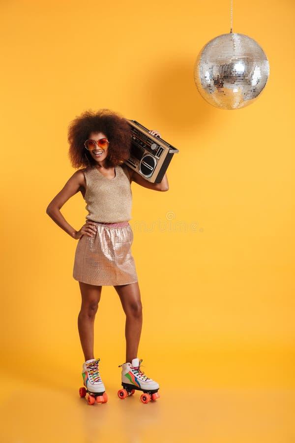 Full längdstående av den gladlynta afrikanska diskokvinnan med handnolla arkivbilder