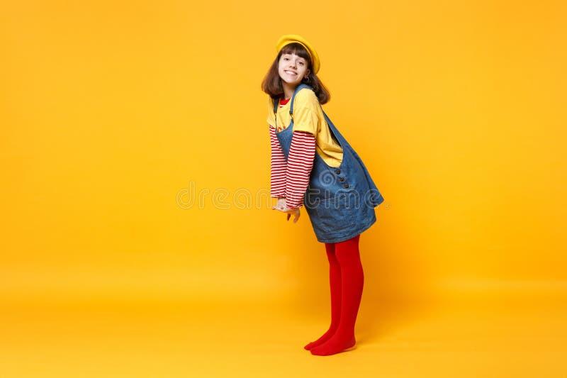 Full längdstående av den härliga flickatonåringen i franskt basker- och grov bomullstvillsundressanseende som isoleras på den gul arkivfoto