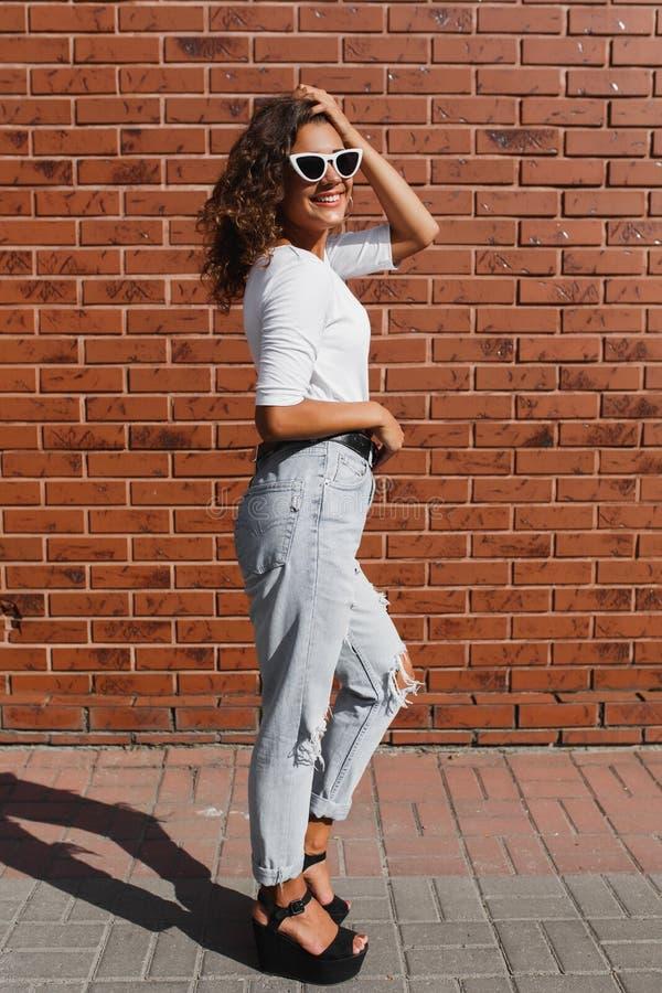 Full längdstående av den härliga gulliga unga kvinnan med långt lockigt hår i den vita t-skjortan fotografering för bildbyråer