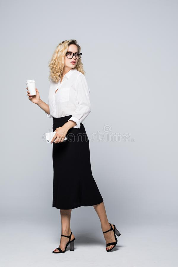 Full längdstående av den härliga unga affärskvinnan i formella kläder som går och smsar på mobiltelefonen med takeaway kaffe i mu royaltyfri fotografi