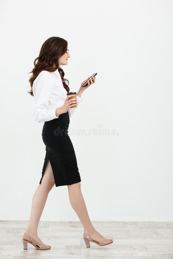 Full längdstående av den härliga unga affärskvinnan i formella kläder som går och smsar på mobiltelefonen med takeawayen fotografering för bildbyråer