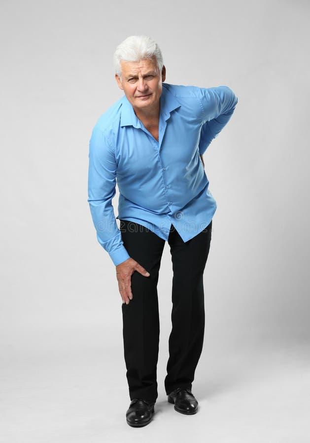 Full längdstående av den höga mannen som har knäproblem arkivbilder