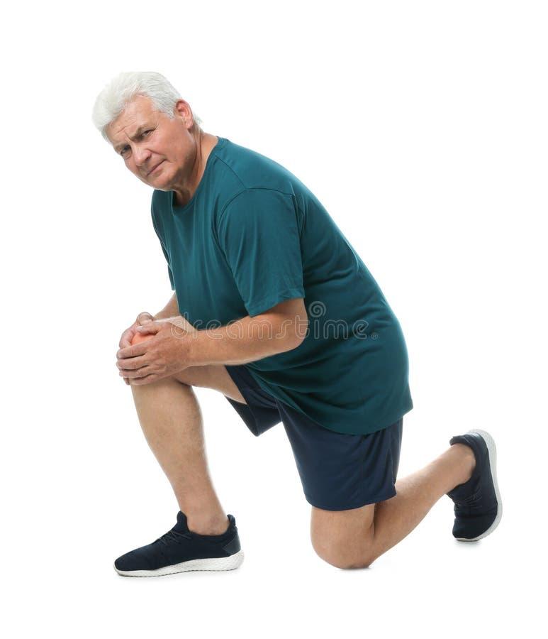 Full längdstående av den höga mannen som har knäproblem arkivfoto