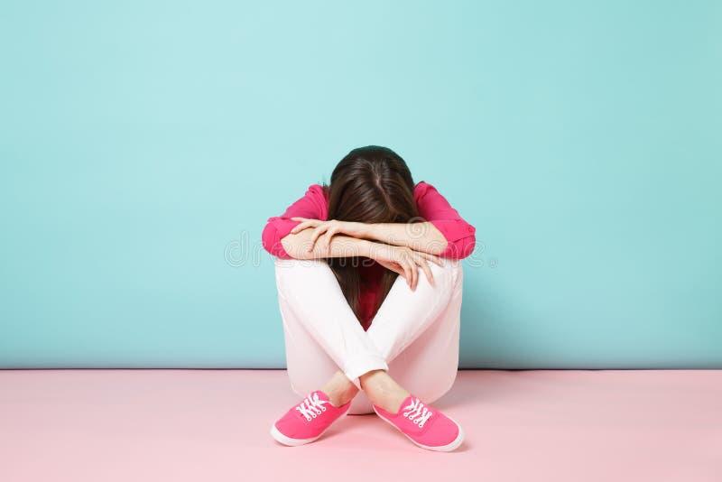 Full längdstående av den ledsna upprivna unga kvinnan i den rosa skjortablusen, vita flåsanden som sitter på golvet som isoleras  royaltyfri foto