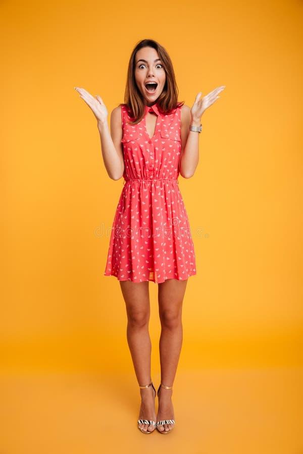 Full längdstående av den lyckliga förvånade flickan i röd klänningstandi fotografering för bildbyråer