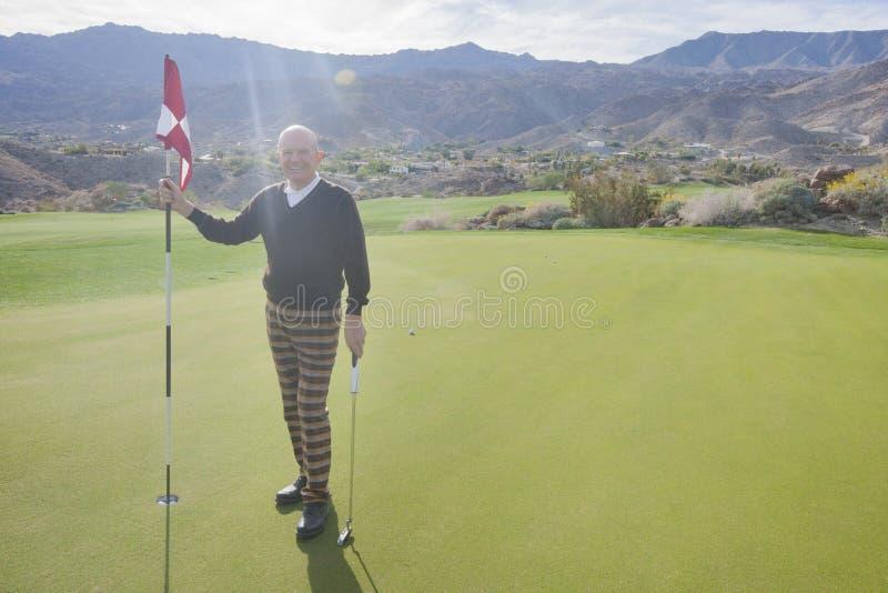 Full längdstående av den lyckliga höga manliga golfareinnehavflaggan och putter på golfbanan royaltyfria foton