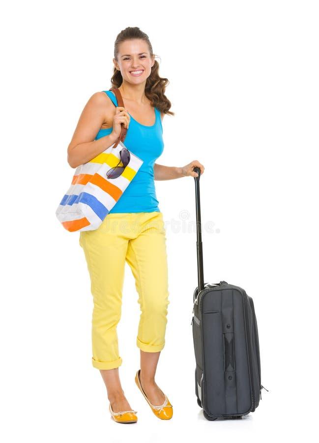 Full längdstående av den lyckliga unga turist- kvinnan med hjulpåsen arkivfoton
