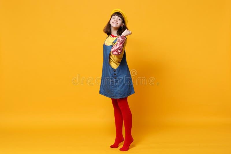 Full längdstående av den nätta flickatonåringen i den franska basker, grov bomullstvillsundress som rymmer hår på den gula väggen fotografering för bildbyråer