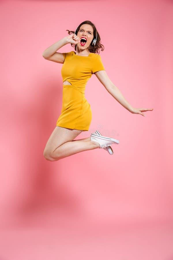 Full längdstående av den nätta unga kvinnan i hörlurar som har arkivfoto