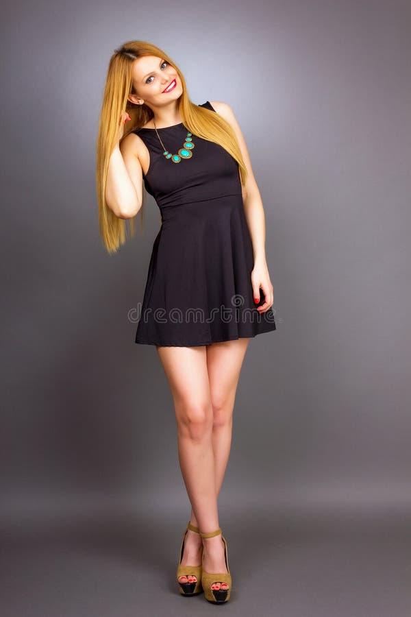 Full längdstående av den sexiga unga blonda kvinnan som bär en kortkort royaltyfria bilder