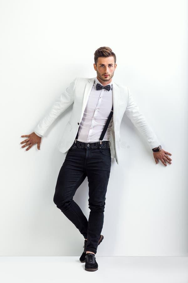 Full längdstående av den stiliga mannen i den vita eleganta dräktposinen royaltyfri fotografi